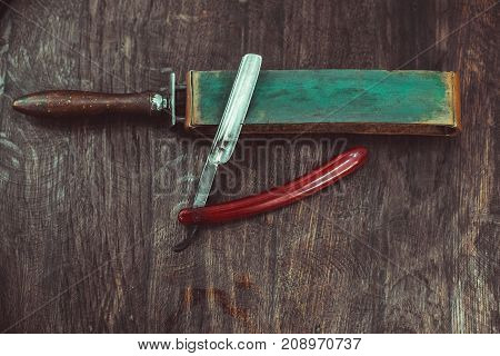 Vintage dangerous razor with leather sharpener on a wooden background