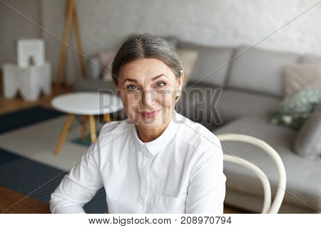Headshot of successful positive mature 60 year old European woman life coach consultant or psychologist in formal blouse waiting for client at home office looking at camera with confident smile