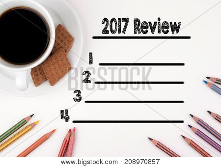 2017 review blank list. White desk with a pencil and a cup of coffee.