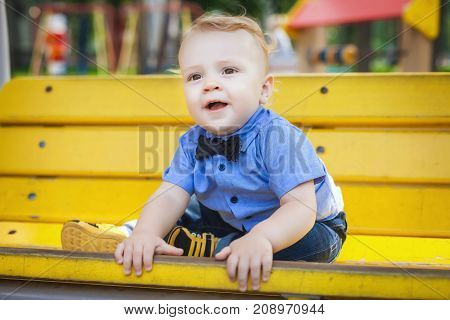 handsome boy sitting on yellow bench in amusement park, beautiful child walking with his parents in park, concept of happy family