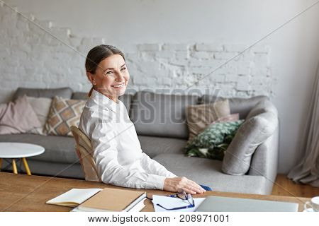 Picture of cheerful middle aged school psychologist having rest at her study sitting at desk with copybook notes and laptop computer. Beautiful senior female freelancer taking notes working at home