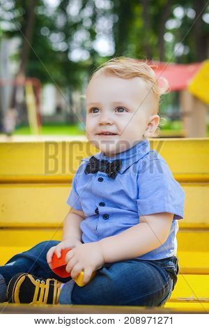 cute boy sitting on yellow bench in amusement park, nice child playing with toy in park, concept of happy family