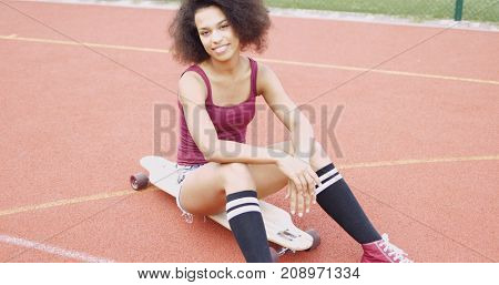 Young model in casual summer clothing sitting on longboard on sports ground and looking confidently at camera.