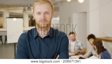 Young bearded man in shirt holding hands together posing inside of modern office with coworkers at table on background.