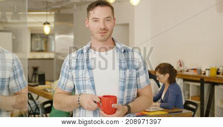Young casual man holding red mug looking at camera and posing in modern office with coworkers on background.
