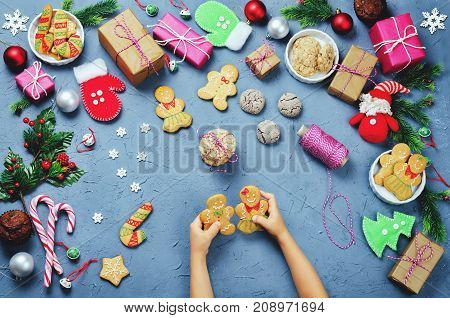Christmas background with gifts cookies Christmas decoration and children's hands holding gingerbred cookies