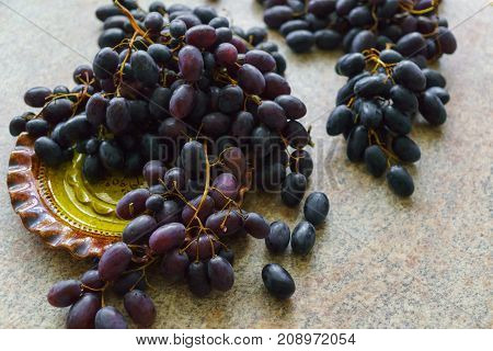 Clusters of fresh sweet dark grapes lying on the table.