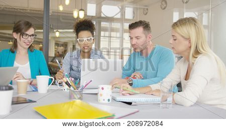 Young multiethnic people sitting at table in contemporary office and working with documents while watching laptop together.