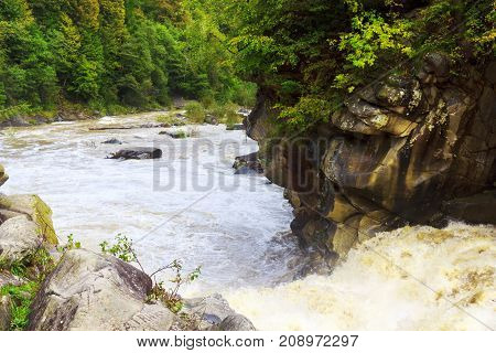 cascade on a fast mountain river among the forest and rocks