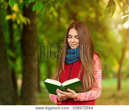 Young romantic girl standing with an open book at sunset. The book is shooting from behind the girl's shoulder