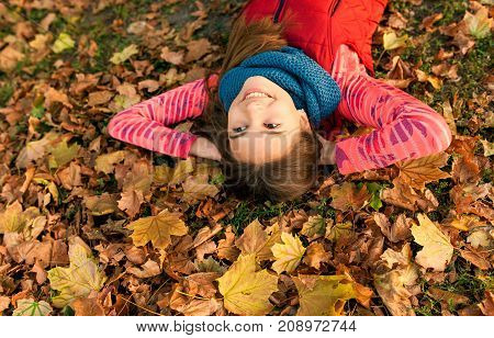 Smiling young girl lying down on autumn maple leaves at fall outdoors. Portrait of a beautiful smiling teenage. Young teenager girl looking to camera. Autumn, winter season.