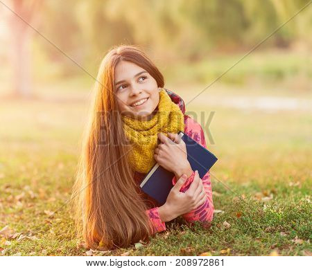 Portrait of a young girl reading a book on a background of autumn colour park. Young woman portrait in autumn color. People concept