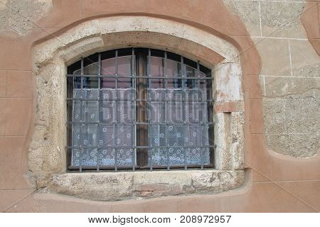 The picture was taken in the old part of Budapest called Buda. In the photo the window of an old house is behind bars.
