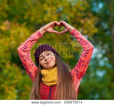 young girl making hands in heart shape in autumn color. woman autumn portrait. Autumn woman having fun at the park and smiling.