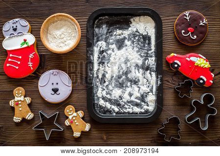 Make gingerbread cookie for new year 2018. Gingerbread man, flour on dark wooden background top view.