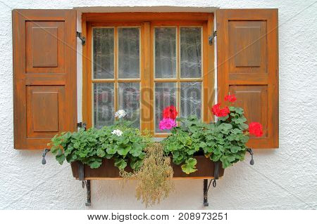 The picture was taken in the German countryside. The picture shows a traditional village house window. It opened the shutters and is decorated with flowers.