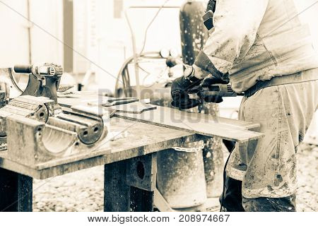 Closeup cutting plate steel with anglegrinder old style workplace image monochrome
