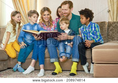 Family reading a book. People sitting on the sofa. How to acquire wisdom.