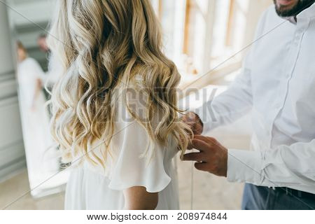Groom helps fasten a wedding dress the bride before the ceremony. Wedding concept. Artwork Back view, close-up