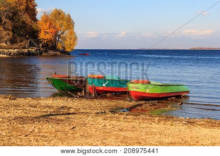 Moored to the stony shore of the boat, anchored on the shore against the backdrop of a forested slope, a river and sky. Autumn