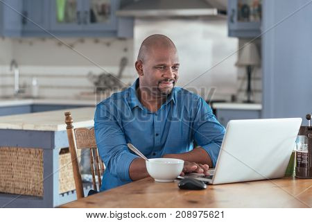 Smiling mature African man browsing online with a laptop while sitting at his kitchen table eating breakfast
