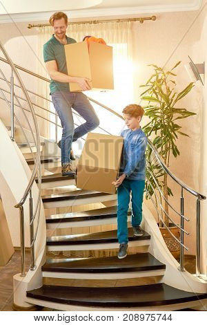 Father and son carrying boxes. Man with a kid, relocation.
