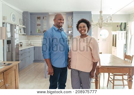 Portrait of an affectionate African couple smiling and holding hands while standing together in their kitchen at home