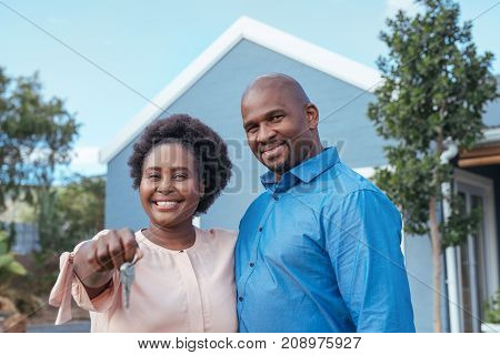 Portrait of a happy African couple standing arm in arm together outside holding the keys to their new home