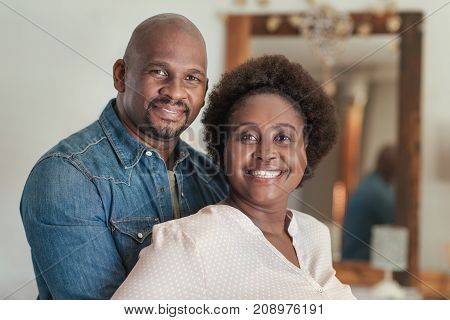Portrait of a content African couple smiling while standing together in their living room at home