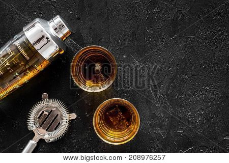 shot of whiskey with ice and barmen equipment on black table background top view space for text