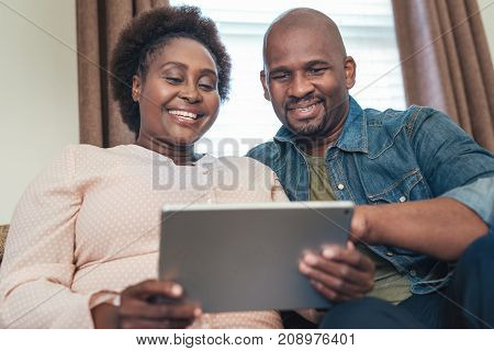 Smiling African couple browsing online with a digital tablet while sitting and relaxing together on their living room sofa at home