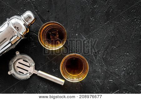 Alcohol cocktails with whiskey and ice, bartender tools on black bar background top view mockup
