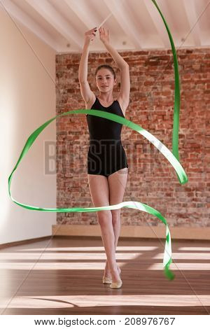 Rhythmic gymnastics. Young ballerina repetition. Teenage sport, healthy teen lifestyle. Confident girl with green ribbon, dance class background, exercise concept