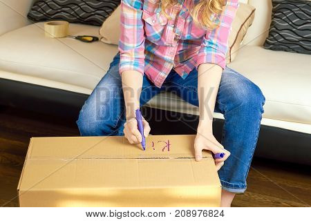 Hands writing on a box. Person getting ready for relocation.