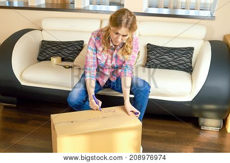 Woman writing on box, relocation. Girl using a marker.