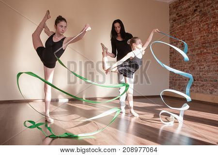 Rhythmic gymnastics. Ballerinas lessons education. Teenage sport, healthy teen lifestyle. Female coach with young girls in motion, dance class background, ballet concept