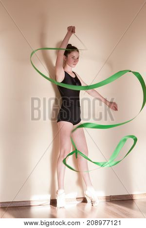 Rhythmic gymnastics. Graceful ballerina in motion. Teenage sport, healthy teen lifestyle. Confident girl with green ribbon, dance class background, exercise concept