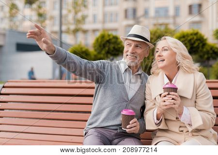 Two pensioners are sitting on a bench with a glass of coffee in their hands. A man smiles shows a woman something ahead of them