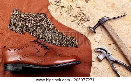 Leather Brogues Shoes On Pieces Of Leather And Nails Ordered In Form Of A Shoe On Table Of Shoemaker