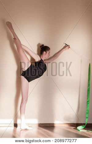 Rhythmic gymnastics. Graceful girl flexibility. Teenage sport, healthy teen lifestyle. Beautiful ballerina with green ribbon, brown background with free space, exercise concept