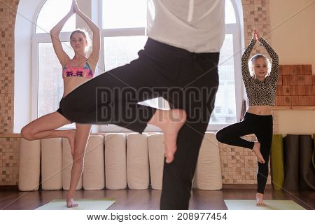 Teenage yoga class. Sport for children. Young girls workout in focus on background with unrecognizable female instructor. Healthy family lifestyle, stretching exercise