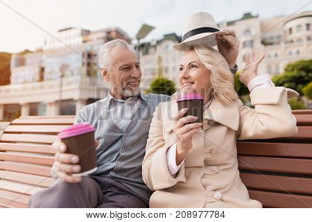 Two pensioners are sitting on a bench with a glass of coffee in their hands. They sit embracing, a man trying on a woman his hat. They are laughing