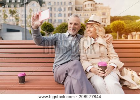 Two pensioners are sitting on a bench with a glass of coffee in their hands. They sit hugging and making selfies on the smartphone of a man.