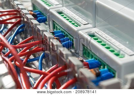 Electric wire laid in the cable channel is connected to the electronic devices. Connect wires to modular metering devices on a mounting panel in electrical closet. Red wire and blue with the tips.