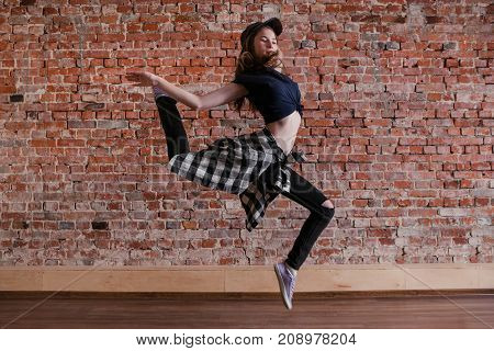 Dance is freedom. Lightness in life. Happiness in moving, sporty teenage girl on brick wall background with free space. Hip hop lifestyle, dancing young female, breakdance concept
