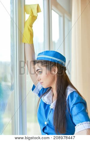 Tired young housemaid. Woman looking out the window. Fatigue symptoms at work.