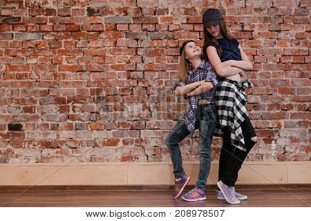 Friendship in style. Urban dance. Hip hop for teenagers, stylish happy girls in studio. Brick wall background with free space. Joyful street life, fashion concept