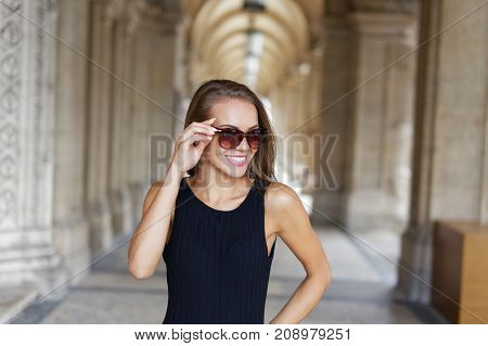 Woman smiling while taking on glasses at vault outdoor architecture building in city