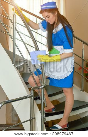 Young housemaid with rag working. Woman wipes railing.