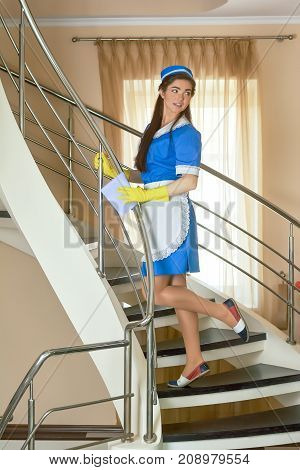 Attractive housemaid working. Young woman on stairs. Foolproof flirting tips.